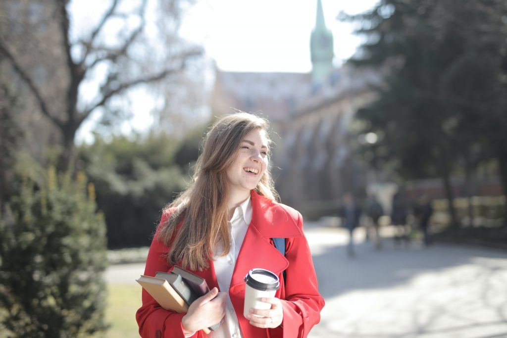university student holding coffee glad she received a prepaid card